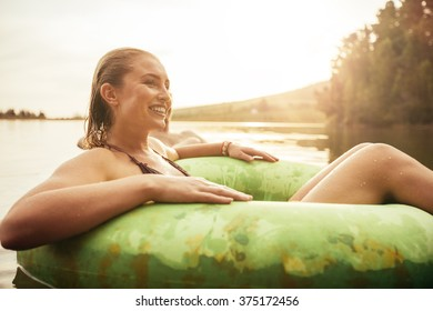 Portrait of happy young woman in lake on inflatable ring looking away and smiling. Young girl relaxing in water on a summer day.