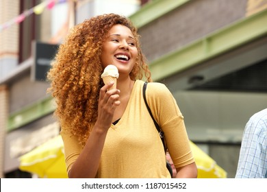 Portrait of happy young woman laughing with ice cream in the city