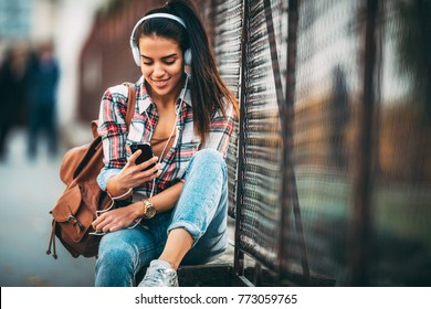 Portrait of a happy young woman listening to music via headphones on the street