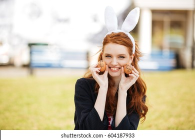 Portrait of a happy young woman with long ginger hair and bunny ears showing painted easter eggs outdoors