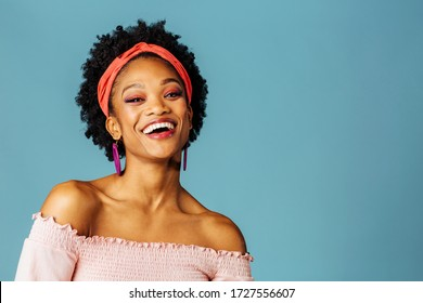 Portrait of a happy young woman with loop earrings laughing and looking at camera isolated on blue color background