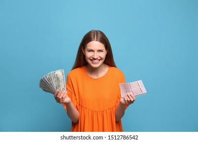 Portrait of happy young woman with lottery ticket and money fan on light blue background