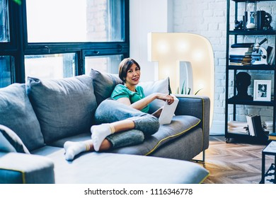 Portrait of happy young woman lying on comfortable sofa and spending leisure time on reading book in apartment.Positive beautiful hipster girl with bestseller smiling at camera relaxing at home
