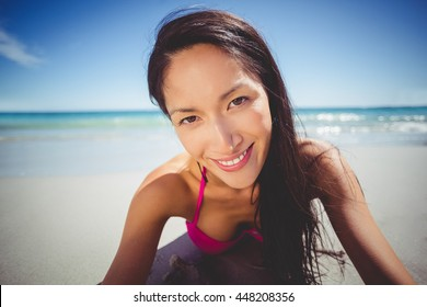 Portrait of happy young woman lying on beach