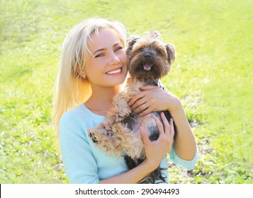 Portrait of happy young woman owner with yorkshire terrier dog in the park