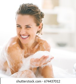 Portrait of happy young woman playing with foam in bathtub