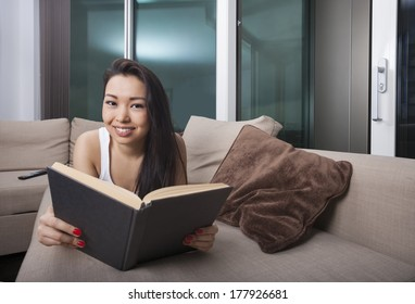 Portrait of happy young woman reading book while lying on sofa
