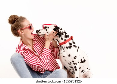 Portrait of happy young woman in red glasses sitting with her dalmatian dog, that licking her face. Copy space, friendship concept