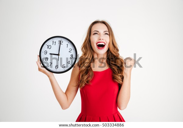 Portrait of happy young woman in red santa claus dress holding wall clock and celebrating success over white background