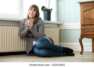 Portrait of a happy young woman relaxing at home with a cup of tea
