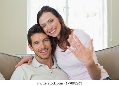 Portrait of a happy young woman showing engagement ring besides man at home