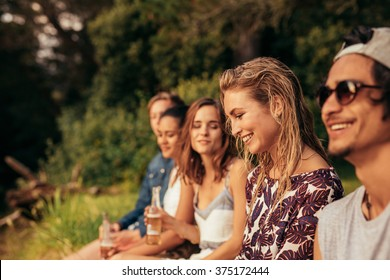 Portrait of happy young woman sitting with her friends by a lake. Young people hanging out at the lake.