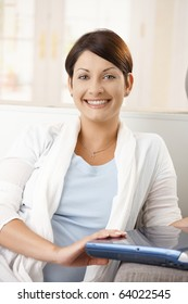 Portrait of happy young woman sitting on couch at home, holding laptop computer, smiling.?