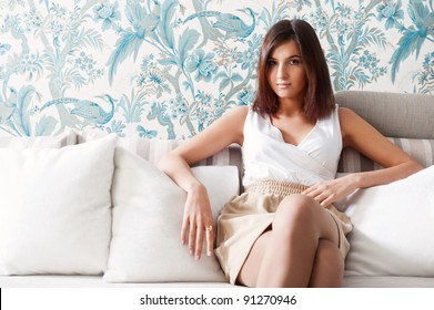 Portrait of happy young woman sitting on sofa at her home