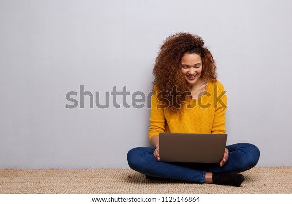 Portrait of happy young woman sitting on floor with laptop
