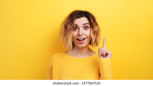 Portrait happy young woman slow motion of finding solution Idea pointing forward an index finger on isolated yellow background, looking directly at the camera smiling. Monotone. Emotions of people