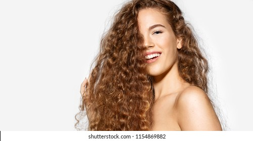 Portrait of happy young woman smiling on camera on white background. Model with curly red hair and perfect skin.  Haircare concept.