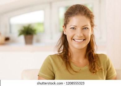 Portrait of a happy young woman, smiling, looking at camera.