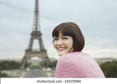 Portrait of a happy young woman smiling in front of Eiffel Tower