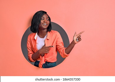 Portrait of happy young  woman smiling and pointing two fingers aside on coral background. Copy space.