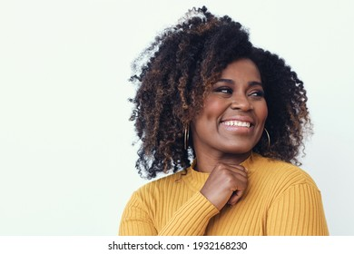 Portrait of a happy young woman smiling dressed in a yellow shirt, looking right
