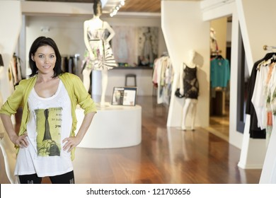 Portrait of a happy young woman standing with hands on hips in fashion clothing store