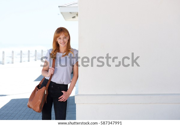 Portrait of happy young woman standing outside leaning on wall