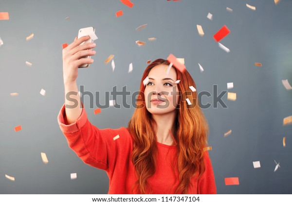 Portrait of a happy young woman  taking a selfie under confetti rain isolated over blue background
