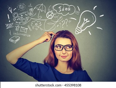 Portrait happy young woman thinking dreaming has many ideas looking at plan isolated grey wall background. Decision making process concept.