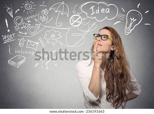 Portrait happy young woman thinking dreaming has many ideas looking up isolated grey wall background. Positive human face expression emotion feeling life perception. Decision making process concept.