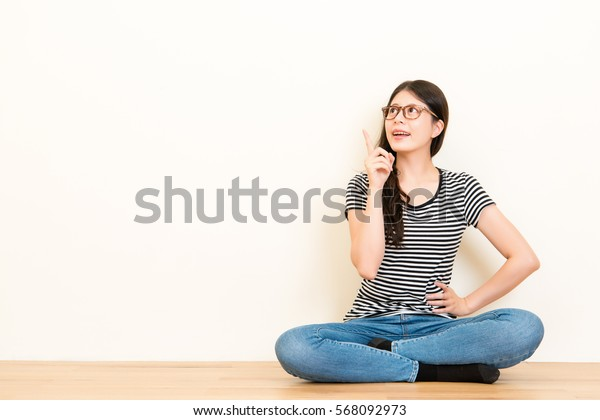 Portrait happy young woman in t-shirt and blue jeans sitting on the floor pointing at copy space. Smiling girl point with finger at blank white copyspace background got new idea.