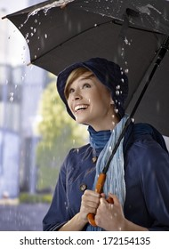 Portrait of happy young woman under umbrella in the rain, smiling.
