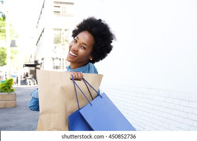 Portrait of a happy young woman walking int he city with shopping bags