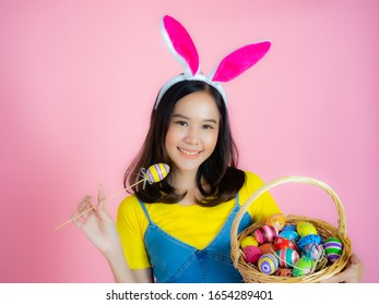 Portrait of a happy young woman wearing Easter bunny ears prepares to celebrate Easter on a pink background.