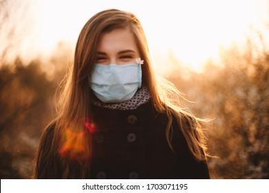 Retrato de una joven feliz con cara protectora y máscara médica de pie en el parque al atardecer durante la primavera
