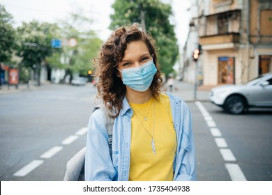 Portrait of happy young woman wearing protective medical mask standing at crosswalk in the city on summer day.