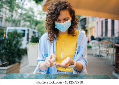 Portrait happy young woman wearing protective medical mask spraying alcohol sanitizer on her hands sitting at table in street cafe in the city at summer day.