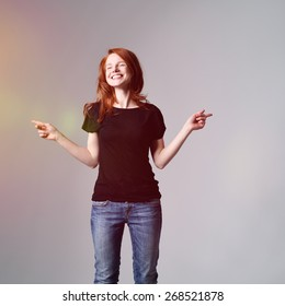Portrait of a Happy Young Woman Wearing Casual Black Shirt and Jeans Pointing her Finger to Both Sides, Captured in Studio with Gray Background and Light From the Left