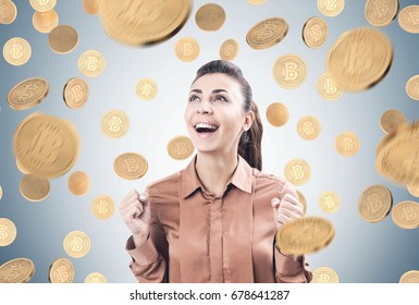 Portrait of a happy young woman wearing a brown blouse and standing under a bitcoin rain near a gray wall.