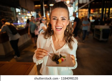 Portrait of happy young woman in white shirt at Mercado San Miguel trying local delicacies