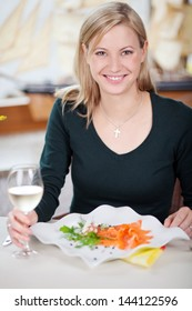 Portrait of happy young woman with white wineglass and food in restaurant