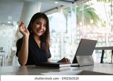 Portrait of happy young woman working on tablet pc while sitting at her working place in office.