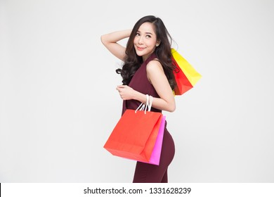 Portrait of a happy young women in red dress holding shopping bags isolated over white background, Year end sale or mid year sale promotion clearence for Shopaholic concept, Asian female model