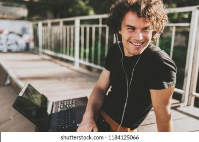 Portrait of hapy male with curly hair using laptop chatting online with friends using earphones to listening the music, connected to free wireless. Male blogger publishing post on website on computer.