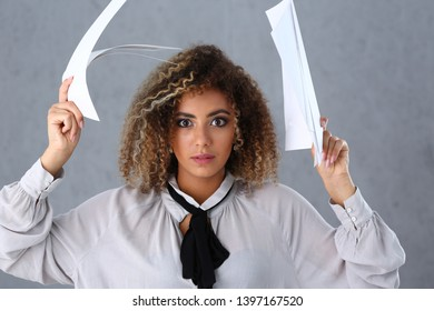 Portrait of hardworking businesslady looking at camera desperately. Curly woman raising documents in great misunderstood. Horrified brunette opened eyes wide. Isolated on grey