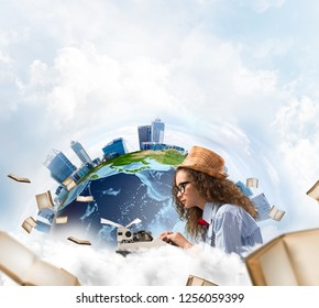 Portrait of hard-working female writer using typing machine while sitting at the table with flying papers and Earth globe among cloudy skyscape on background. Elements of this image furnished by NASA