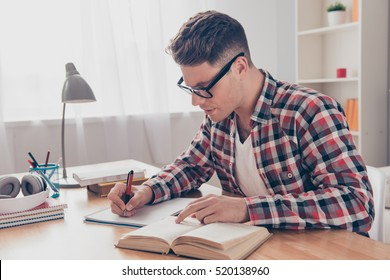 Portrait of hardworking student with book preparing for test in university.
