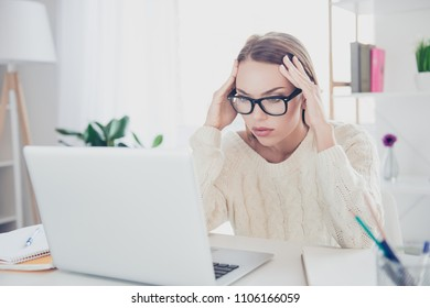 Portrait of hardworking thoughtful writer in glasses looking at screen of laptop having solving trouble sitting in modern workplace workstation trying to find solution decision