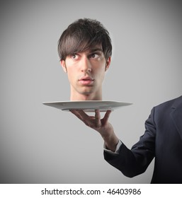 Portrait of the head of a businessman standing on a dish carried by a man's hand