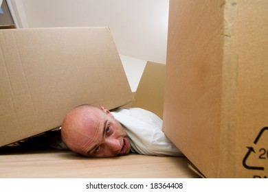 Portrait of head of man with body trapped under cardboard boxes.